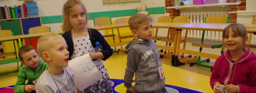 Dzieci siedzące w klasie na podłodze