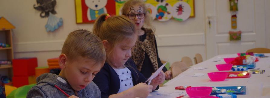 Dzieci siedzące w szkolnychławkach