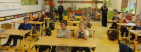 Dzieci z klasy I siedzące w ławkach